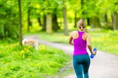 妇女赛跑者跑的跑步在夏天公园 免版税图库摄影