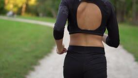 妇女赛跑者运行在公园的,慢动作,后面看法 股票录像