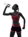 妇女赛跑者连续慢跑者饮用的剪影 免版税库存照片