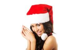 妇女赤裸上身的佩带的圣诞老人帽子 免版税库存图片