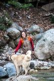 妇女走与两只白种人牧羊犬在森林里 免版税图库摄影