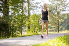 妇女走室外在森林里作为锻炼 库存图片