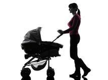 妇女走的摇篮车婴孩剪影 库存图片
