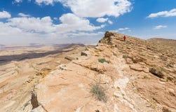 妇女走的沙漠山边缘 库存图片