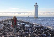 妇女走近到新的布赖顿或者栖息处岩石,灯塔 免版税库存照片