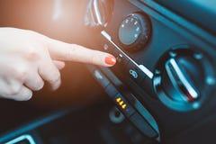 妇女起动在她的汽车的空调 库存图片
