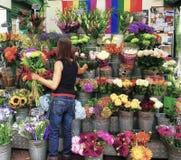 妇女趋向到她的花报亭在伦敦,英国 库存照片