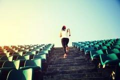 妇女跑在台阶的赛跑者运动员 免版税库存照片