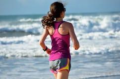 妇女跑在海滩的,跑步女孩的赛跑者户外 免版税库存图片