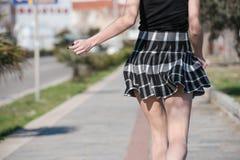 妇女跑掉在有她的微型裙子的边路上下跳跃 库存图片