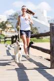 妇女跑步的狗 免版税库存照片