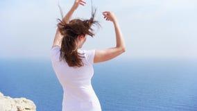 妇女跳充满喜悦在峭壁反对蓝色海在晴天 在慢动作的无忧无虑的女性跳舞 股票视频