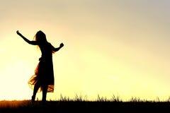 妇女跳舞和称赞上帝剪影在日落 库存图片