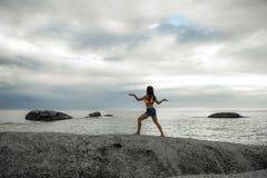 妇女跳舞喜欢岩石的埃及人在Bakovern海滩,开普敦的日落 免版税库存图片