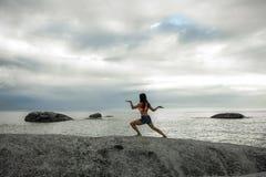 妇女跳舞喜欢岩石的埃及人在Bakovern海滩,开普敦的日落 免版税库存照片
