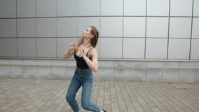 妇女跳舞执行摆在现代节律唱诵的音乐的舞蹈,在街道的自由式,都市 影视素材