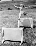 妇女跳跃的障碍标记与几年 免版税库存照片