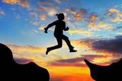 妇女跳过峡谷 库存图片