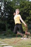 妇女跳绳在庭院里 库存图片