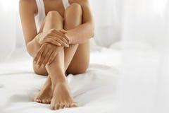 妇女身体关心 关闭有软的皮肤和手的长的腿 免版税图库摄影