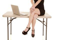妇女身体和腿坐桌计算机 免版税图库摄影