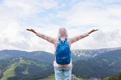 妇女身分后面看法在小山顶部的,感觉自由,摆在与胳膊被舒展对享受风景的天空,夫人穿戴的桃红色 库存照片