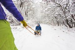妇女身怀雪撬的一个孩子 免版税库存图片