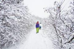妇女身怀雪撬的一个孩子 库存照片