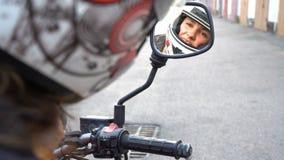 妇女车手定象摩托车盔甲背面图,在摩托车镜子的reflectiong 影视素材
