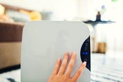 妇女转动在家使用接触控制板的抽湿机 新鲜空气的现代空气干燥器设备 免版税库存照片