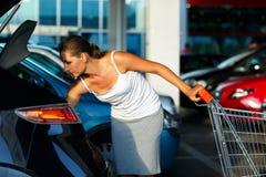 妇女转移从购物车的购买在a.c.树干  图库摄影