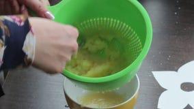 妇女轻拍煮沸的苹果入苹果酱 使用滤锅和匙子 股票录像