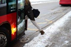 妇女输入的公共汽车在冬天 免版税图库摄影