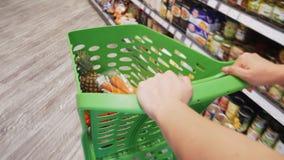 妇女运动的购物的台车特写镜头视图有新鲜的五颜六色的蔬菜和水果的通过超级市场走道  影视素材