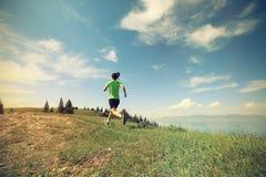 妇女运行在美好的山峰的足迹赛跑者 免版税库存照片