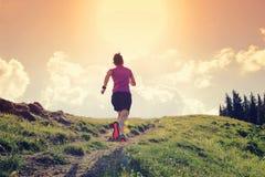 妇女运行在美好的山峰的足迹赛跑者 库存图片