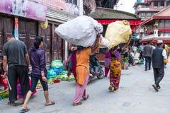 妇女运载在他们的头,尼泊尔的大袋 免版税库存图片