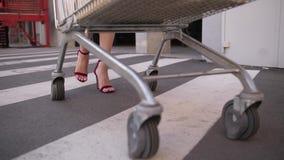妇女运载的手推车的亭亭玉立的腿对汽车的 影视素材
