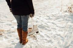 妇女运载的背面图滑冰反对多雪的backgroun 库存照片