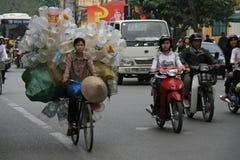 妇女运输在她的自行车的塑料瓶在街道河内(越南) 免版税库存照片