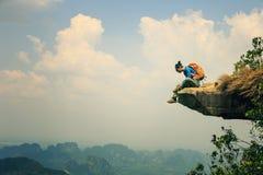 妇女远足者享受在山上面岩石的看法 免版税图库摄影
