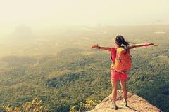 妇女远足者享受在山峰峭壁的看法 库存照片