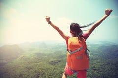 妇女远足者享受在山峰峭壁的看法 免版税库存照片