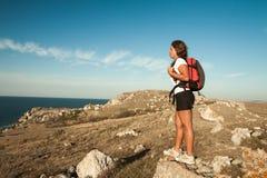 妇女远足者在海边山岩石站立 免版税库存照片