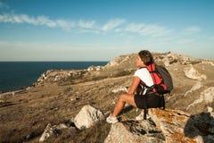 妇女远足者坐海边山岩石 库存图片