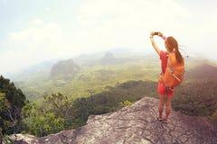 妇女远足者拍在海边山上面的用途智能手机照片 免版税库存图片