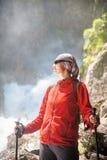 妇女远足者用棍子临近瀑布 蓝色汽车城市概念都伯林映射小的旅游业 库存照片