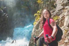 妇女远足者用棍子临近瀑布 蓝色汽车城市概念都伯林映射小的旅游业 库存图片
