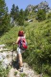 妇女远足者高在指向与她走的杆的山方向 免版税库存照片