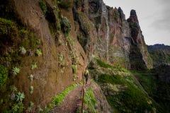 妇女远足者去在陡峭的山边缘 免版税库存照片
